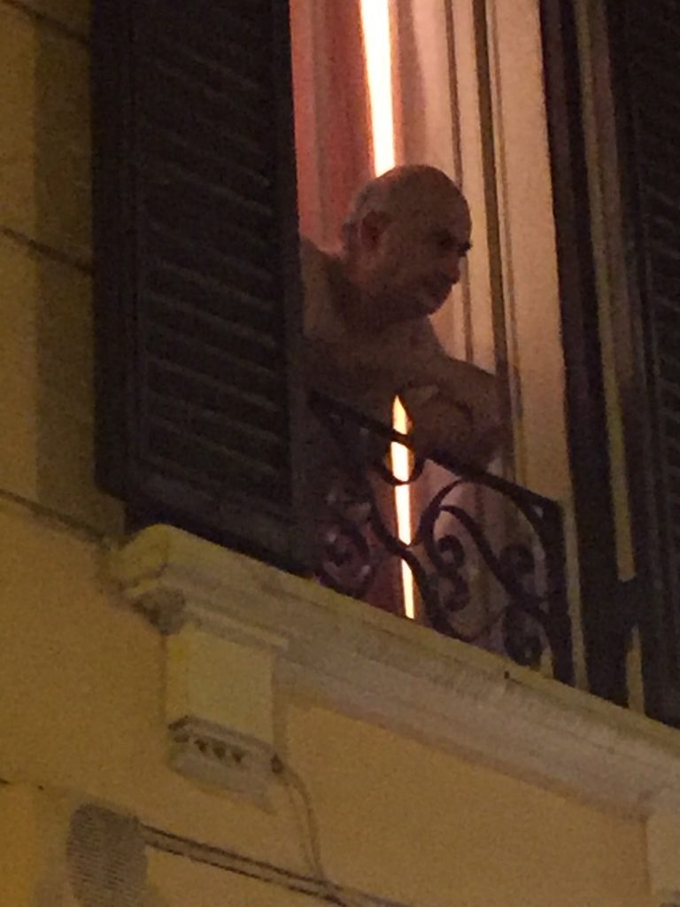 Rome man looking out window no shirt